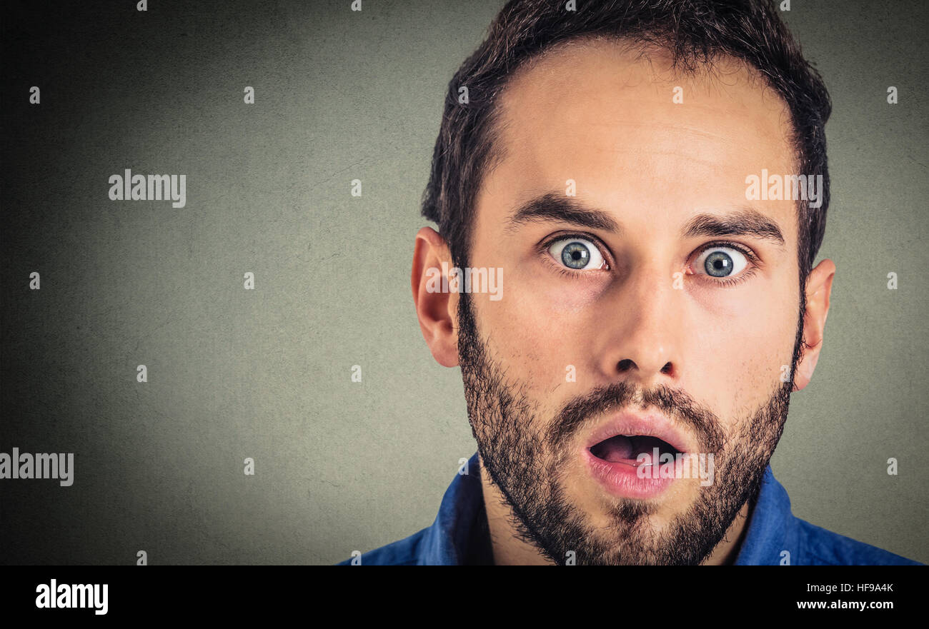Astonished man. Closeup portrait guy looking surprised in full disbelief isolated on grey wall background. Human - Stock Image
