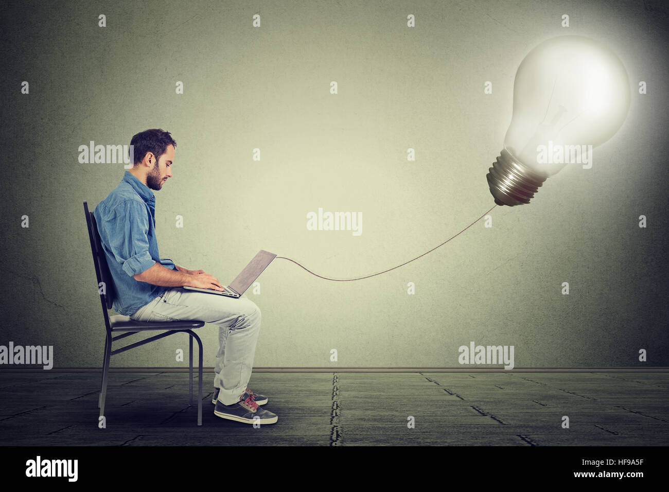Young professional man using a laptop with light bulb plugged in it isolated on gray wall background - Stock Image