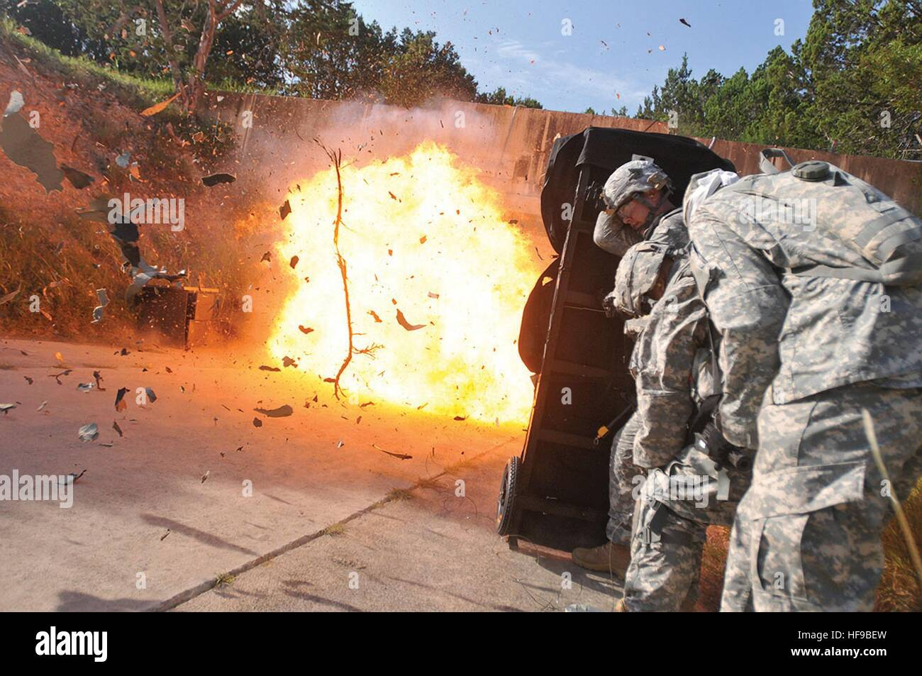 U.S. soldiers find cover behind a blast blanket after detonating an entryway with explosives during a training event - Stock Image