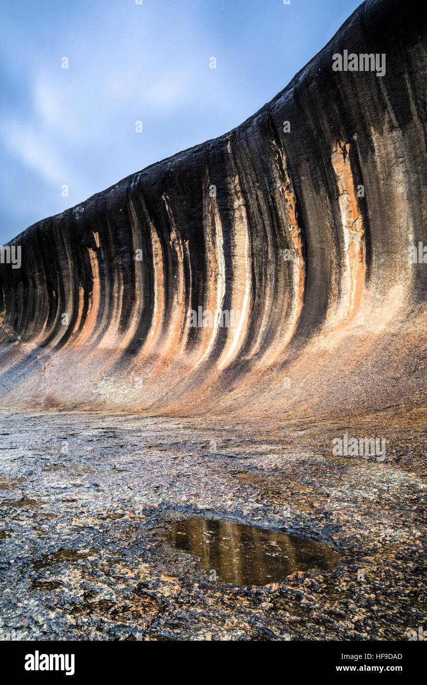 The flared slope of Wave Rock in Western Australia The black stripes are caused by algae discoloration - Stock Image