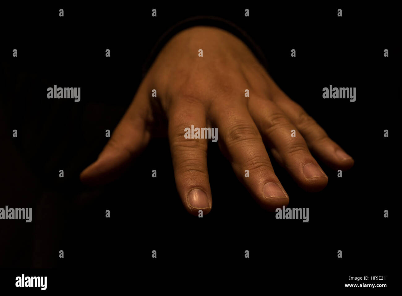 Isolated hand man in the darkness that is becoming diffuse Stock Photo