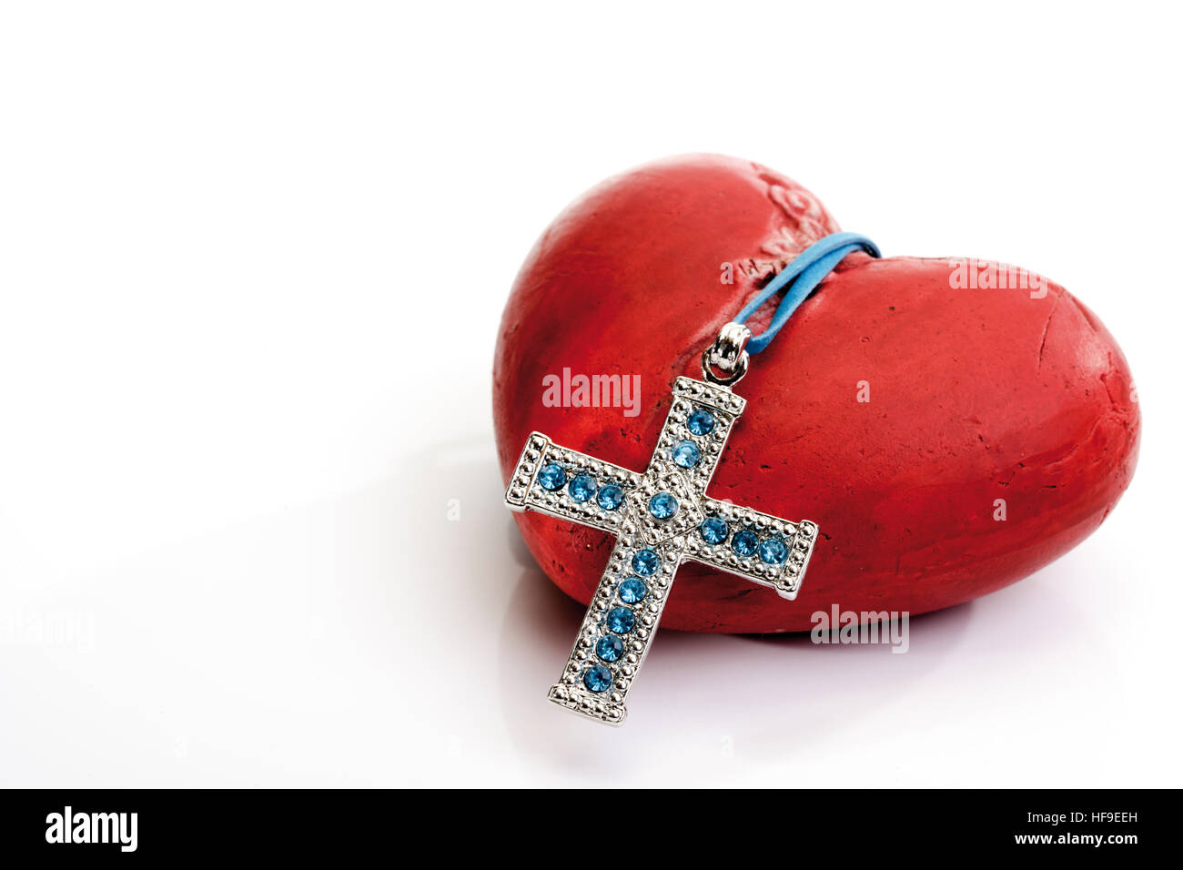 Cross hanging over a heart: godly love Stock Photo