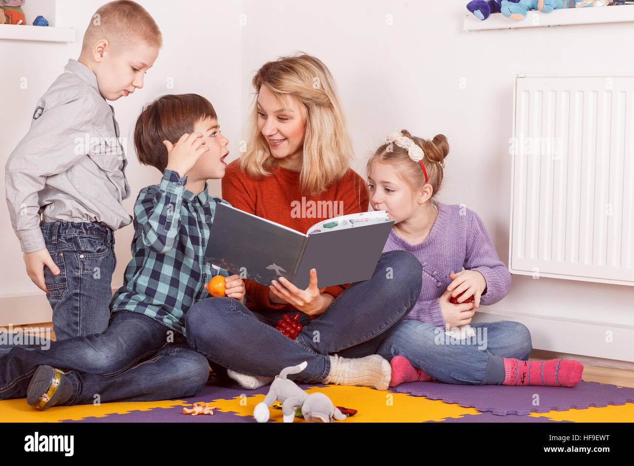 Young woman reading a book with three children - Stock Image