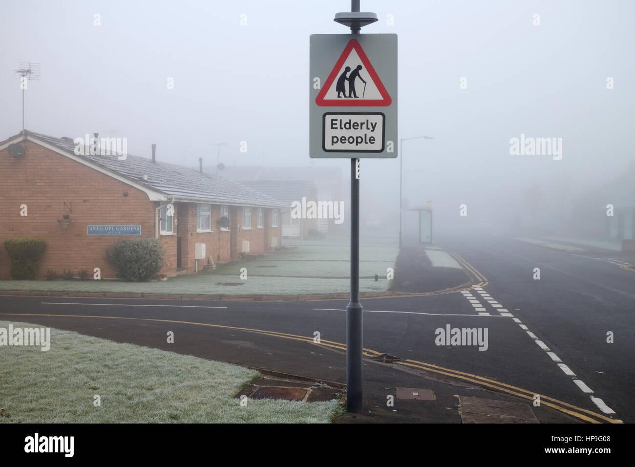 Elderly people road sign in freezing foggy weather by elderly people`s housing, Warwick, UK - Stock Image