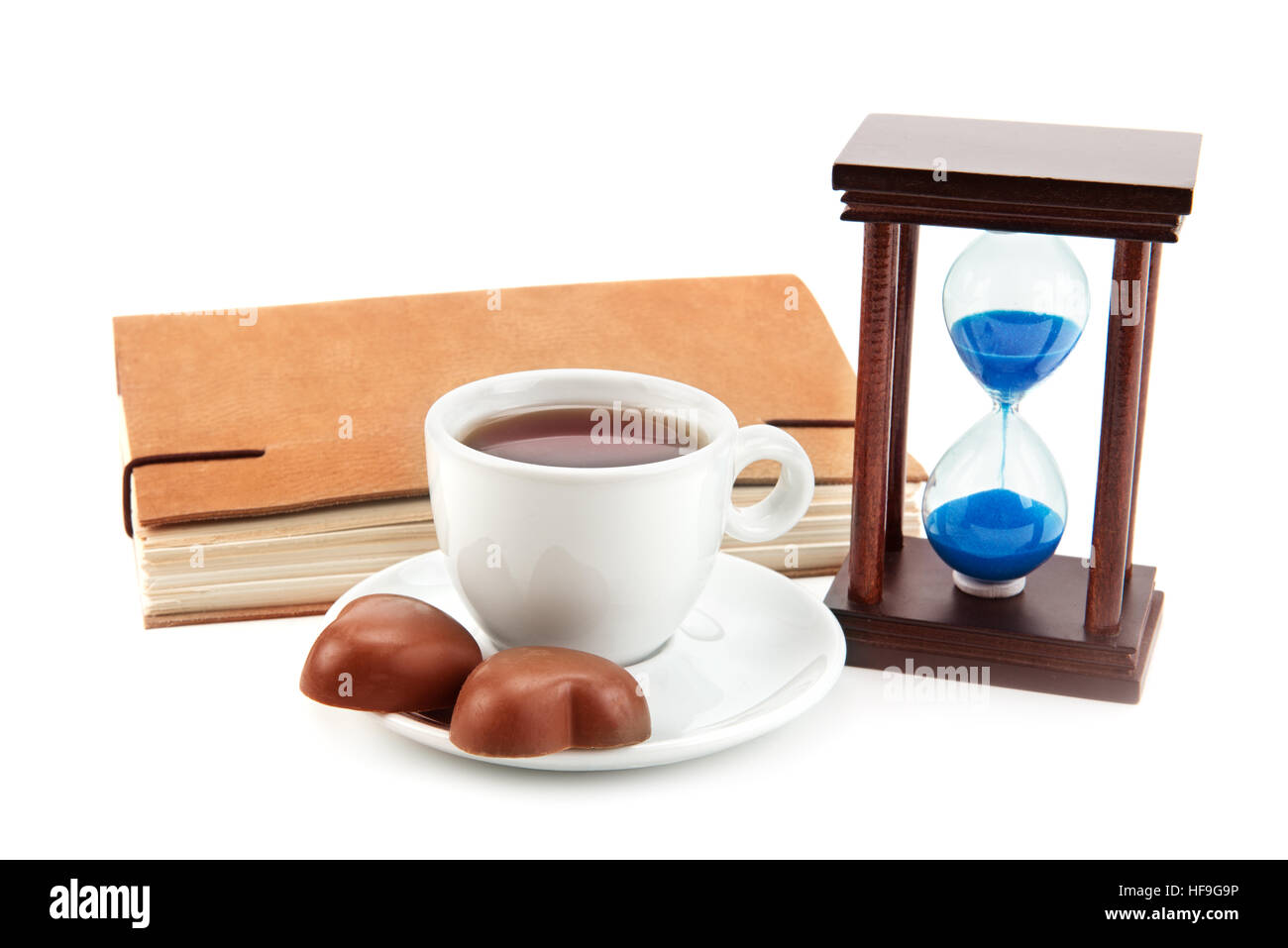 hourglass tea cup and a book on a white background - Stock Image