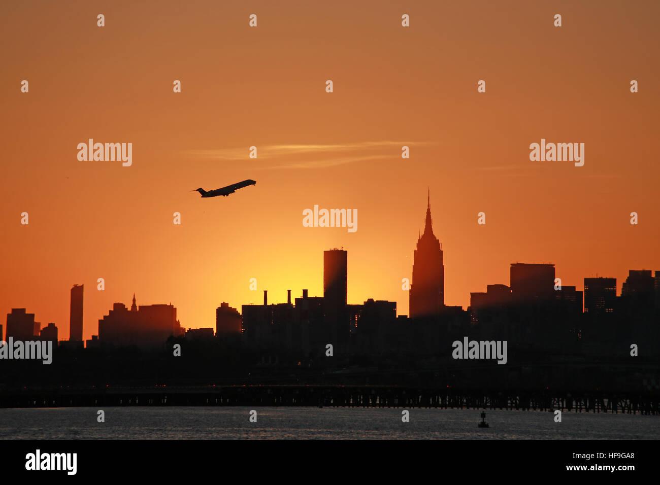 Silhouette of jet taking off over Manhattan skyline, New York, NY, USA Stock Photo