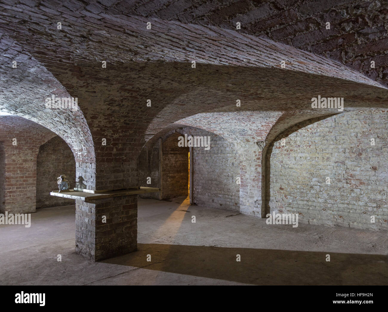 Cellar room made of brick with curved ceiling and an entrance with a  shaft of light beaming in. - Stock Image