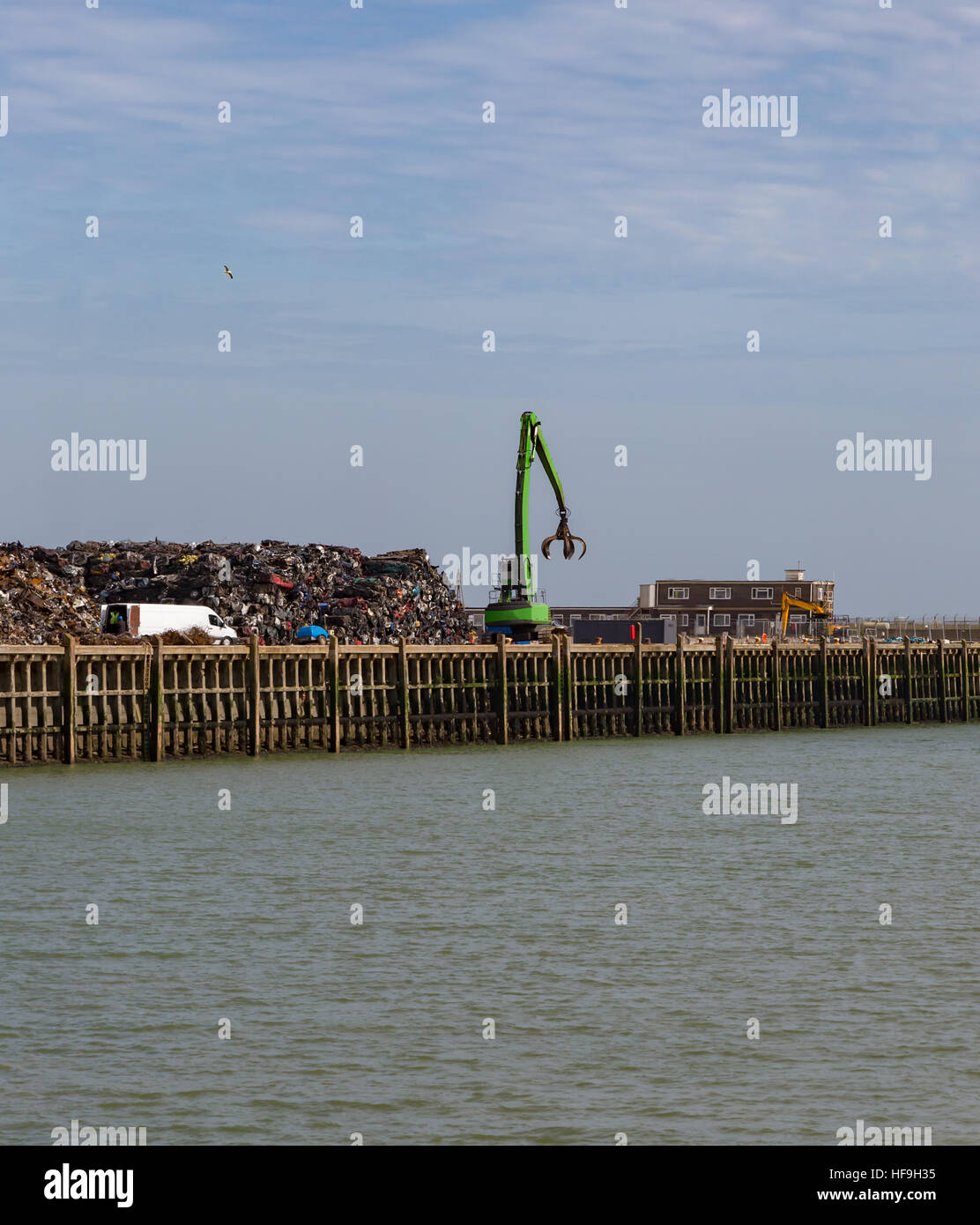 Scrap yard full of crushed cars and the crane with a claw that moves them into a huge pile. By the waterside at - Stock Image