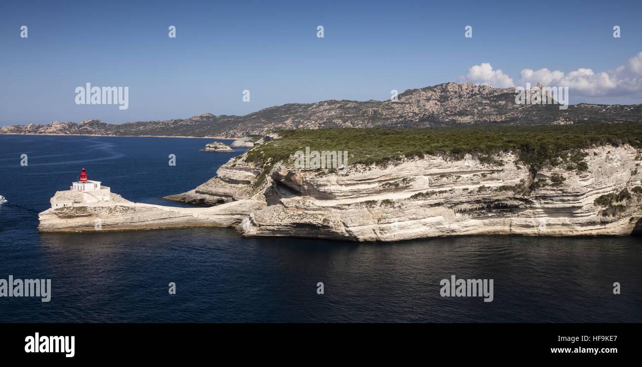 Miocene limestone cliffs north of Bonifacio, with granite hills beyond; Corsica - Stock Image