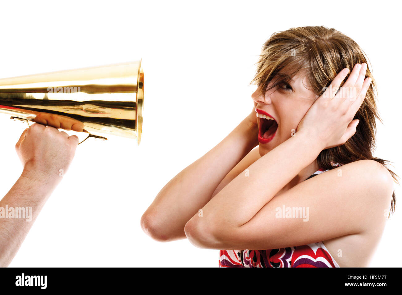 Young woman covering her ears as a man holds a megaphone to her face: noise pollution - Stock Image