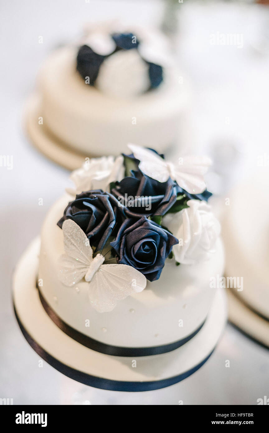 Three white wedding cakes with blue floral decor. - Stock Image