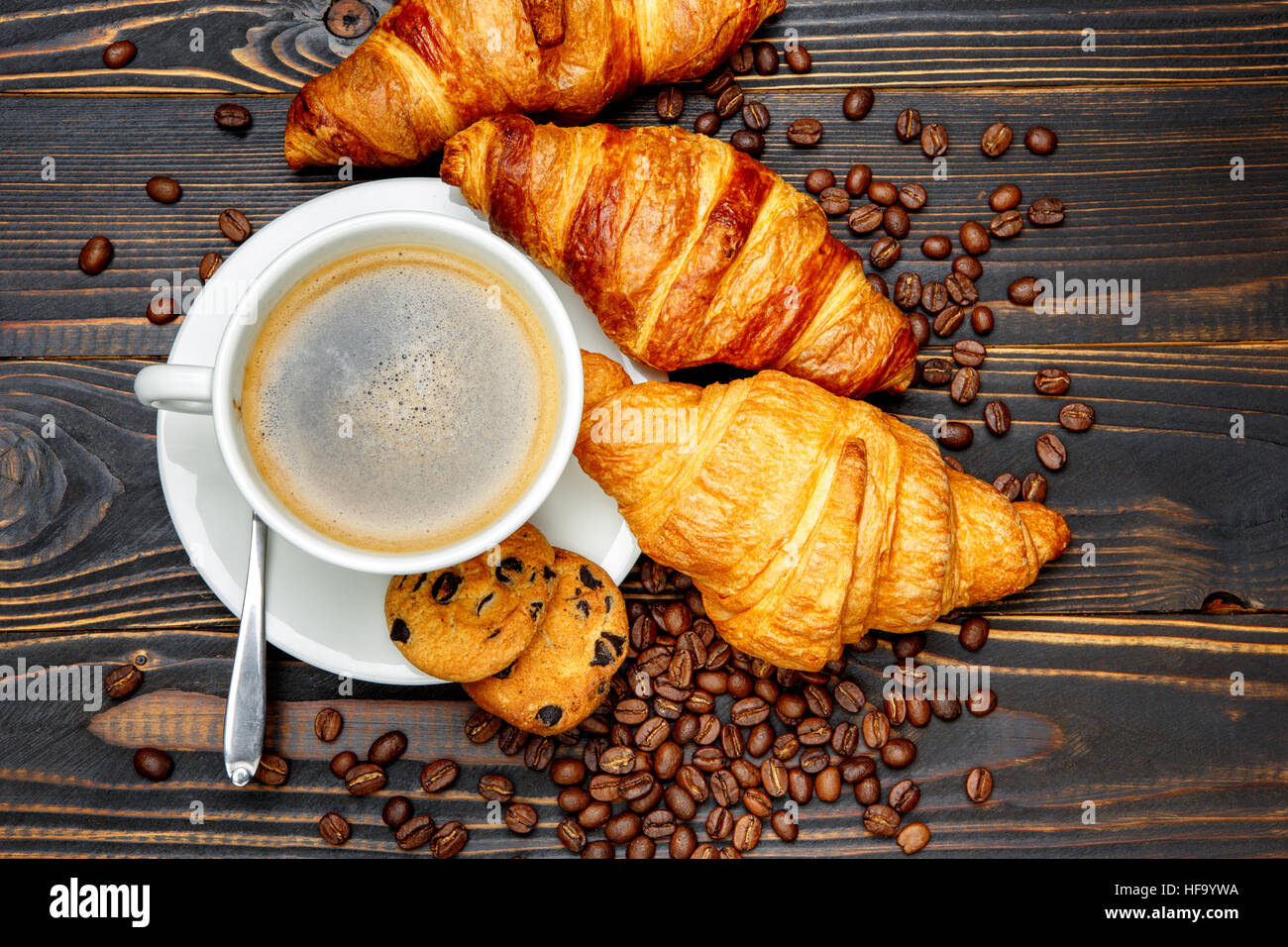 cup of coffe and croissant on wooden background - Stock Image