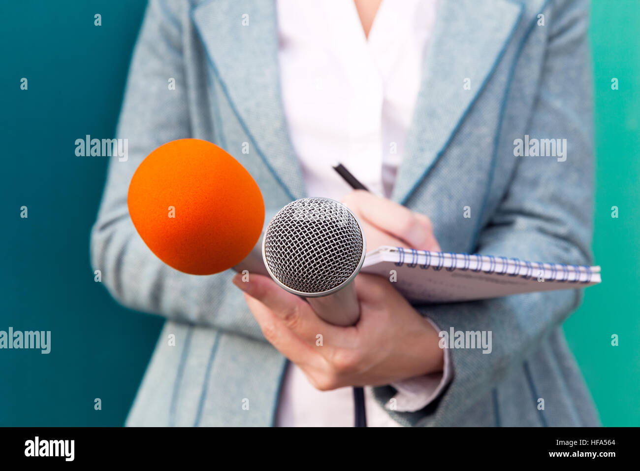 Female reporter taking notes at press conference - Stock Image