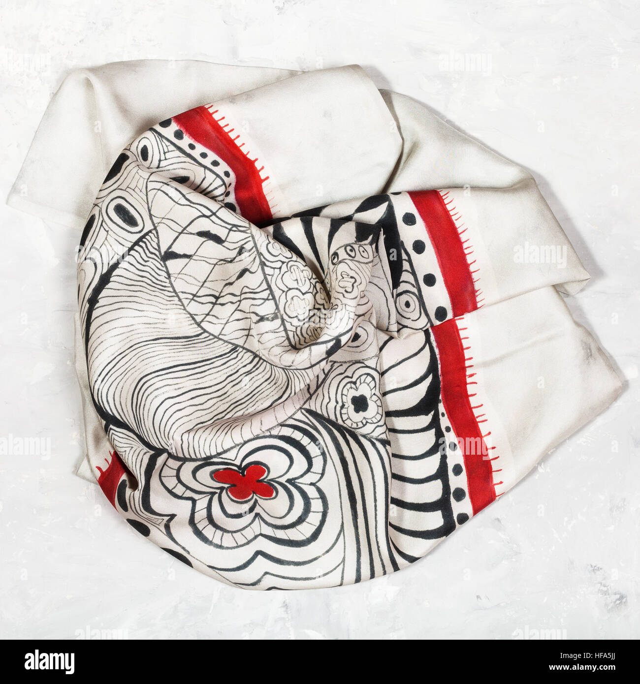 hand painted silk head scarf on concrete plate - Stock Image
