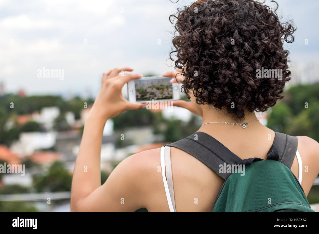 Girl with beautiful short curly hair taking pictures of a city. Using green backpack. Stock Photo