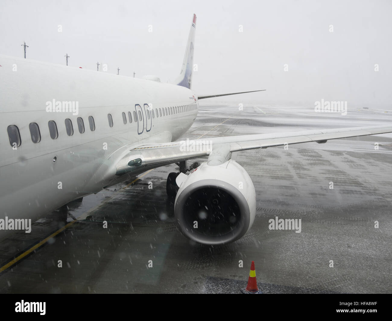 Oslo airport Norway in the wintertime, plane from the company Norwegian ready for boarding in low visibility and - Stock Image