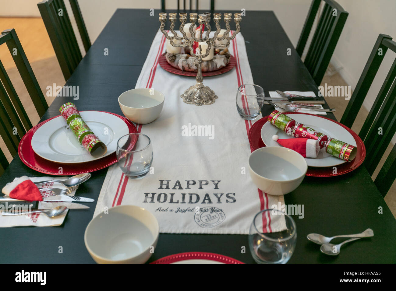 Celebrating Christmas and Hannukah. Decorated Christmas dinner table with a Hannukah Menorah - Stock Image