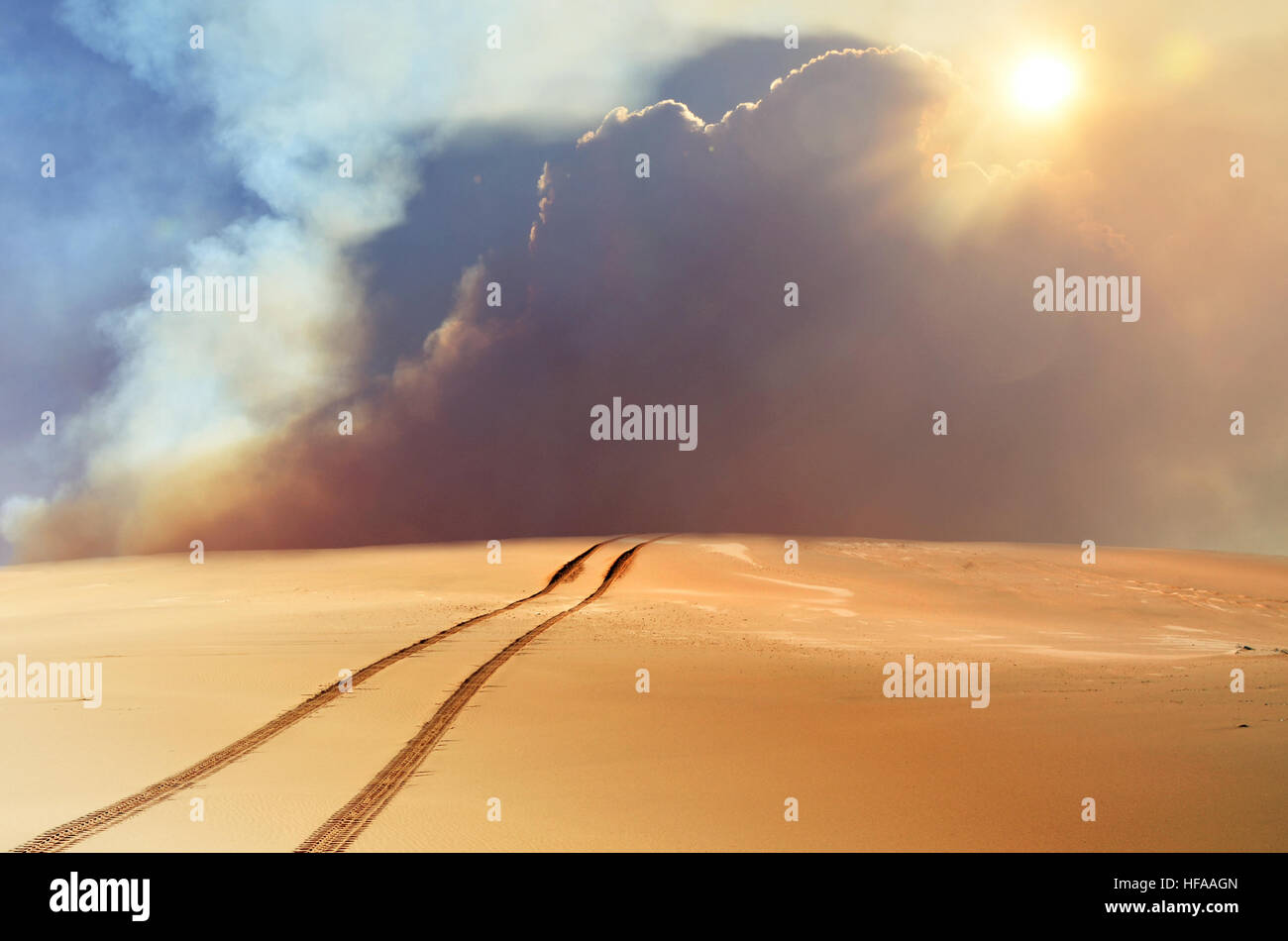 Vehicle tracks through desert and dunes leading into a sand, smoke and cloud filled sky - Stock Image