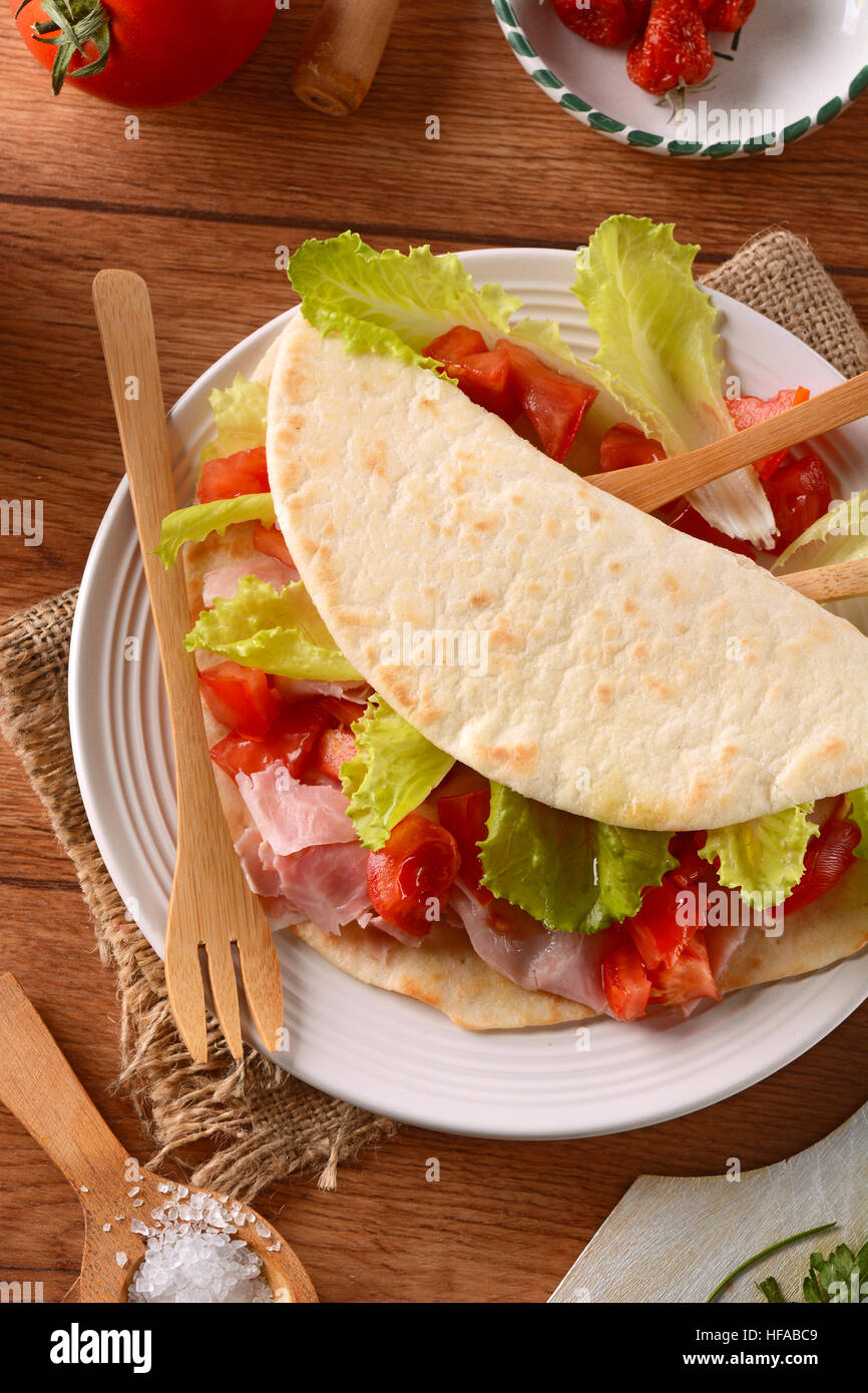 piadina with ham, tomato and vegetables - Traditional Italian recipe - Stock Image