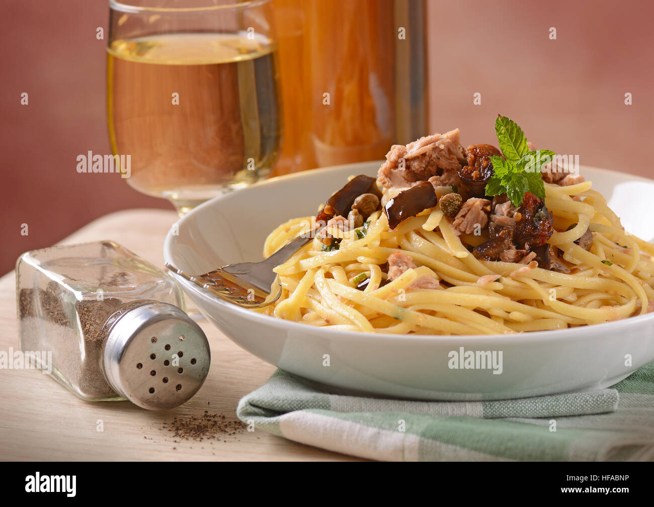 Spaghetti with tuna, capers and eggplant - Traditional Italian recipe - Stock Image