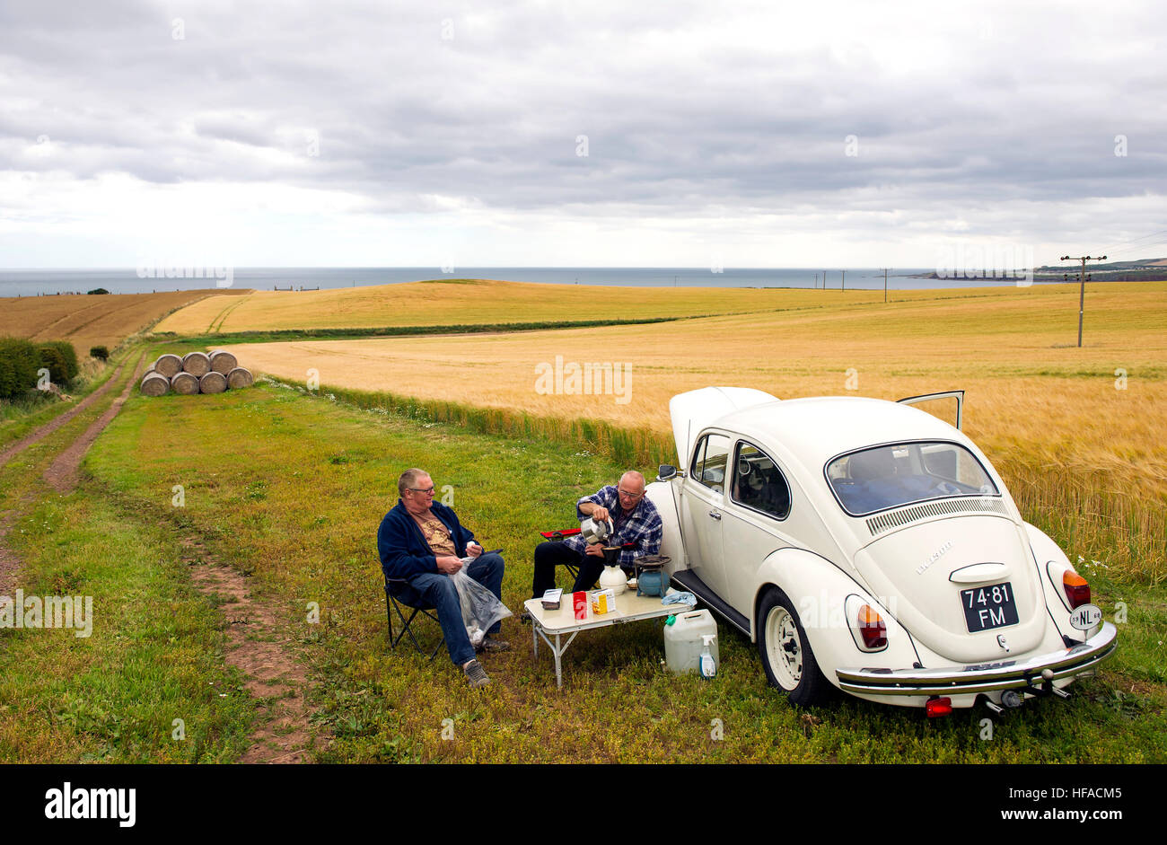 Two Dutch tourists have a picnic beside their VW beetle in a field near St Abbs, Berwickshire, Scottish Borders, - Stock Image