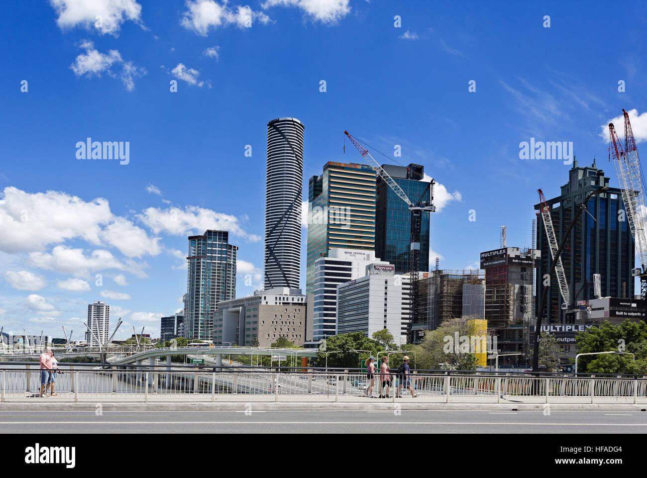 People crossing Victoria Bridge towards the modern city of Brisbane, Australia - Stock Image