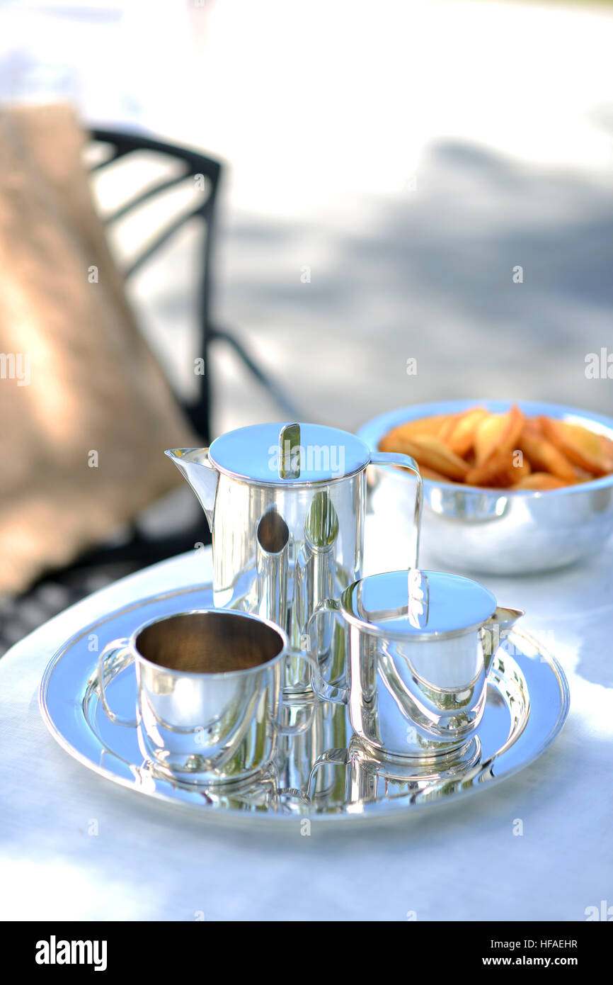 Luxury silver coffee pot on a linen covered table outside in summer. Stock Photo