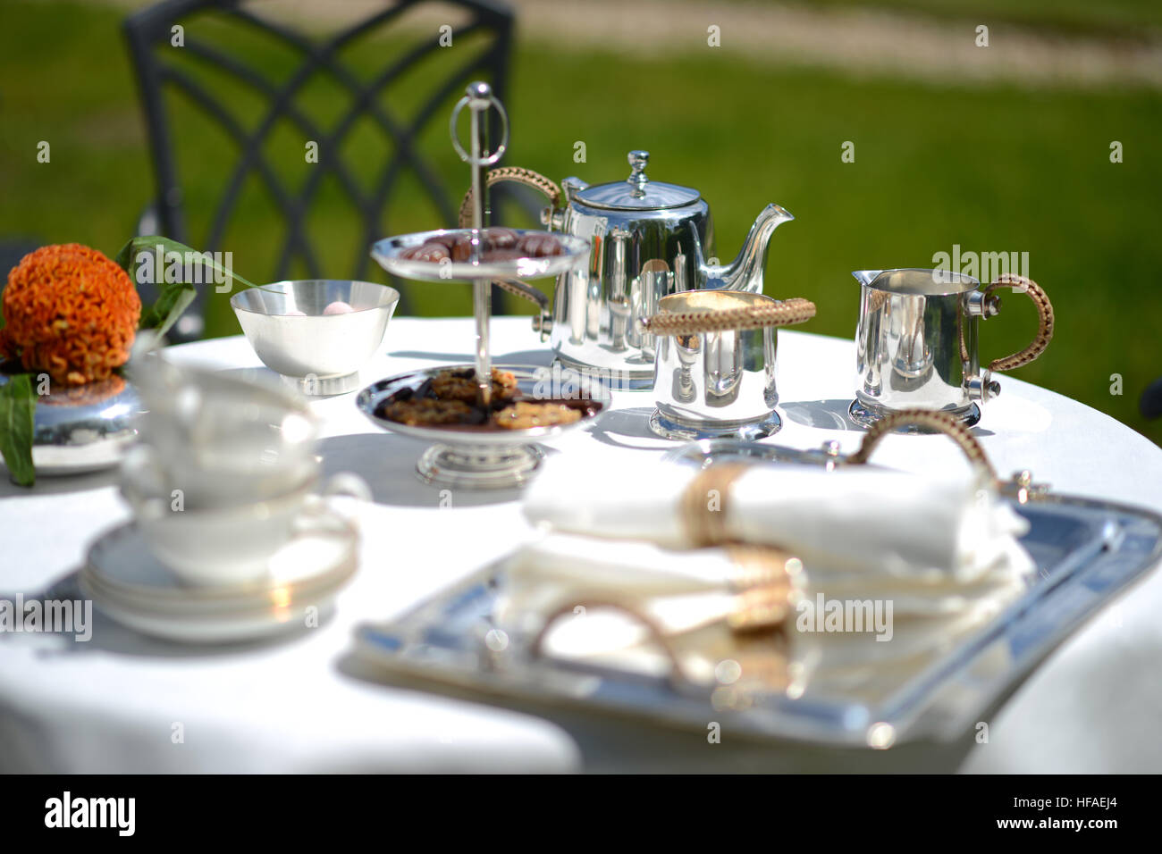 Table set for an English high tea or afternoon tea outside with silver teapot and linen tablecloth & Table set for an English high tea or afternoon tea outside with ...