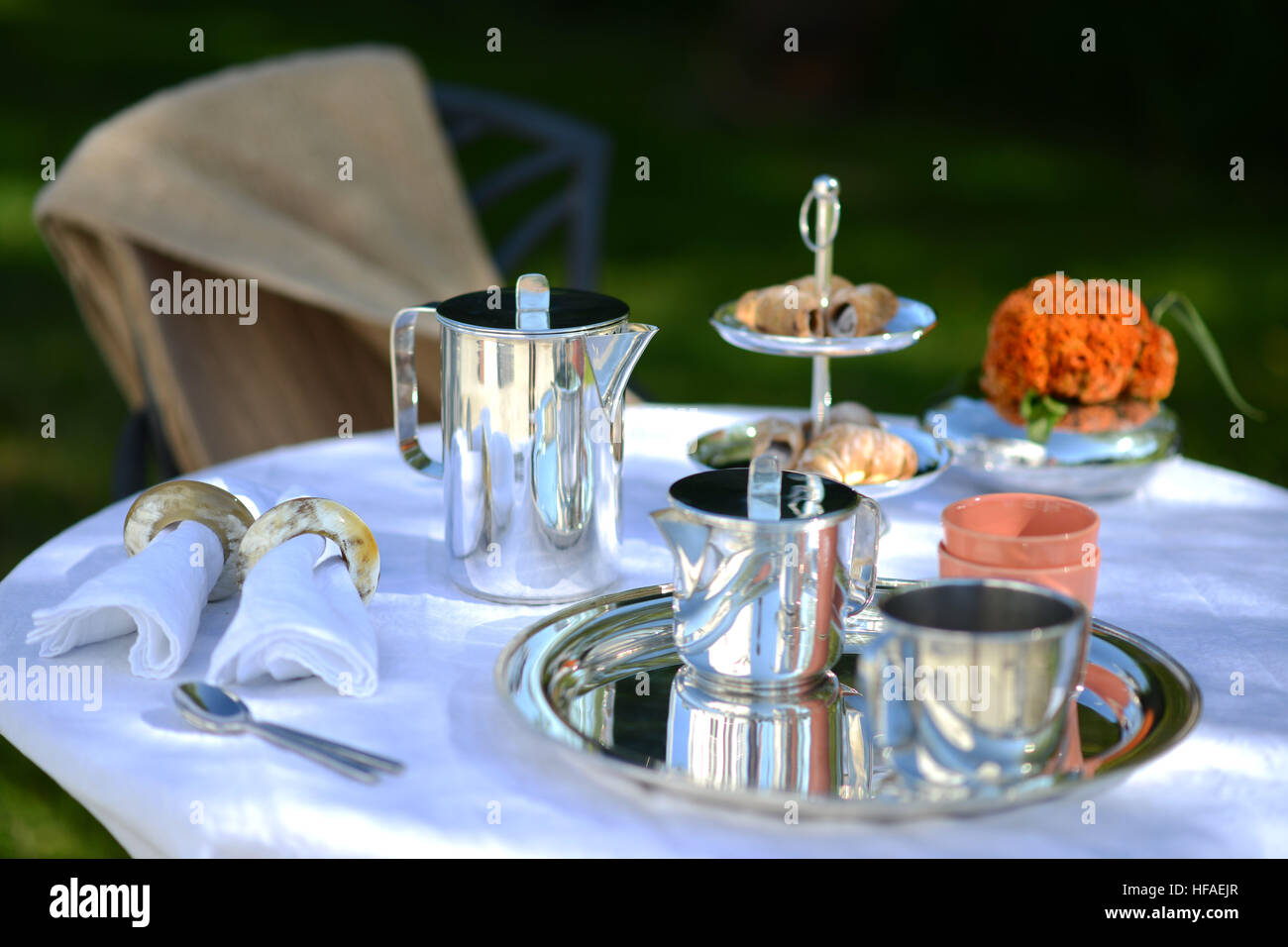 Alfresco coffee from silver coffee pot on linen - Stock Image