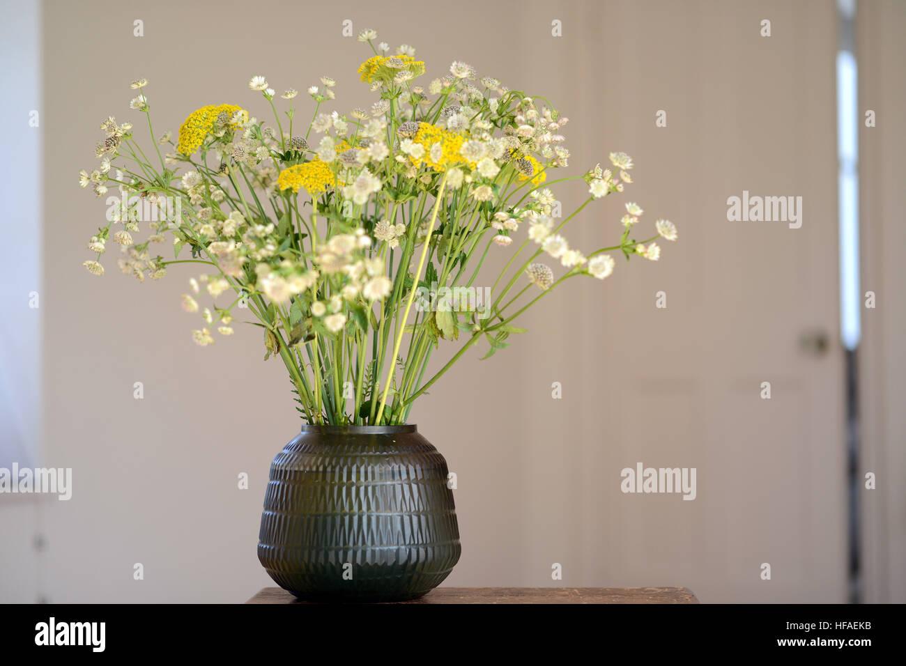 Smokey glass vase with flower display inside - Stock Image
