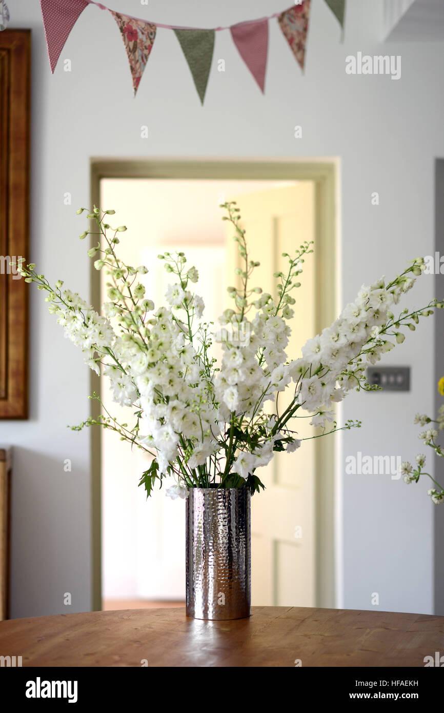 Smokey glass vase with white delphinium flower display inside - Stock Image