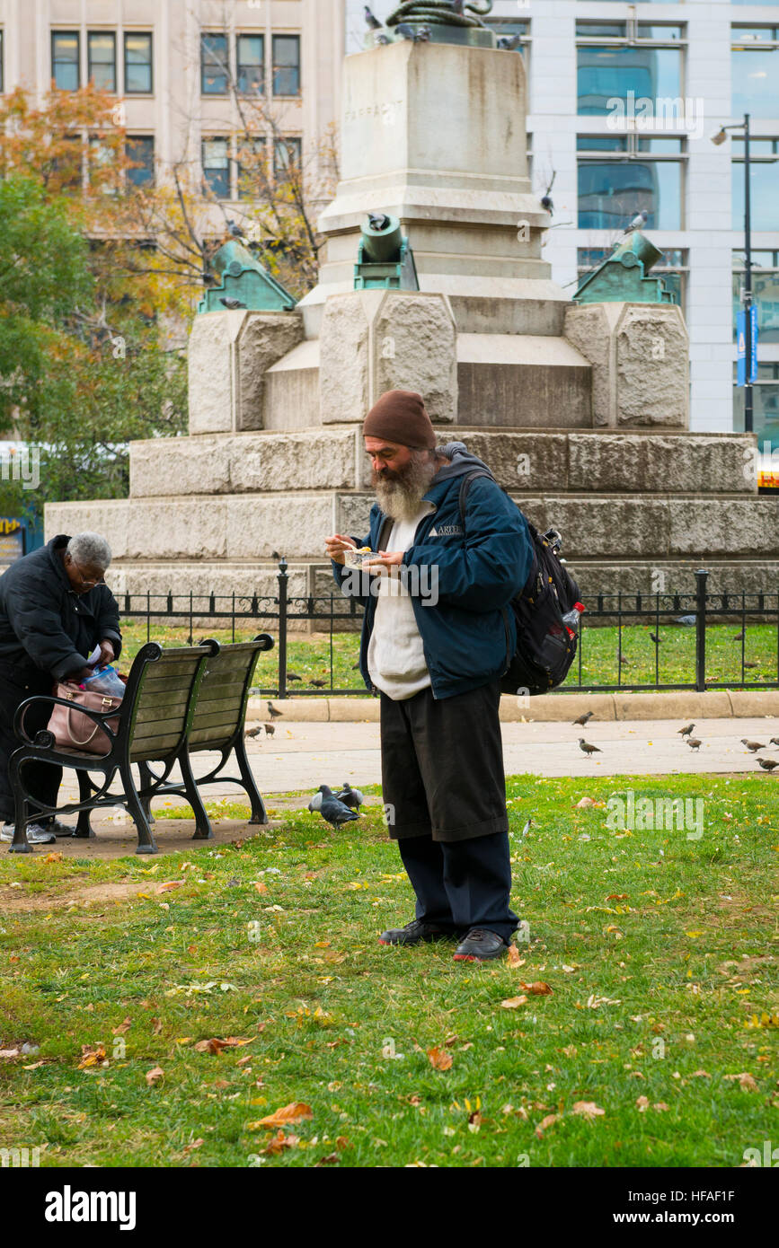 USA capital Washington DC District of Columbia old man male disheveled grey gray beard rucksack hat eating Street - Stock Image