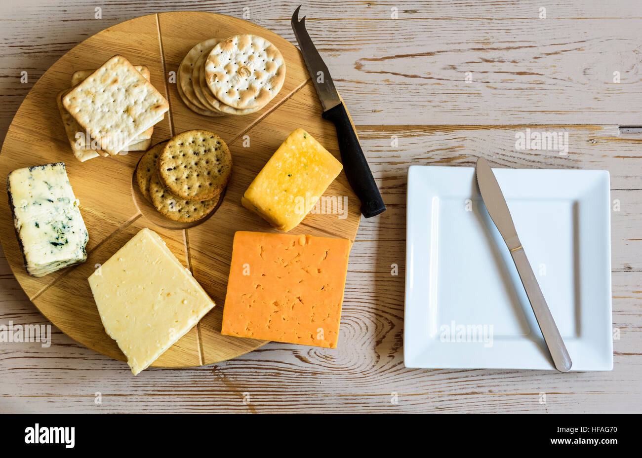 Selection of cheeses on a round cheese board, sitting on an old table. - Stock Image