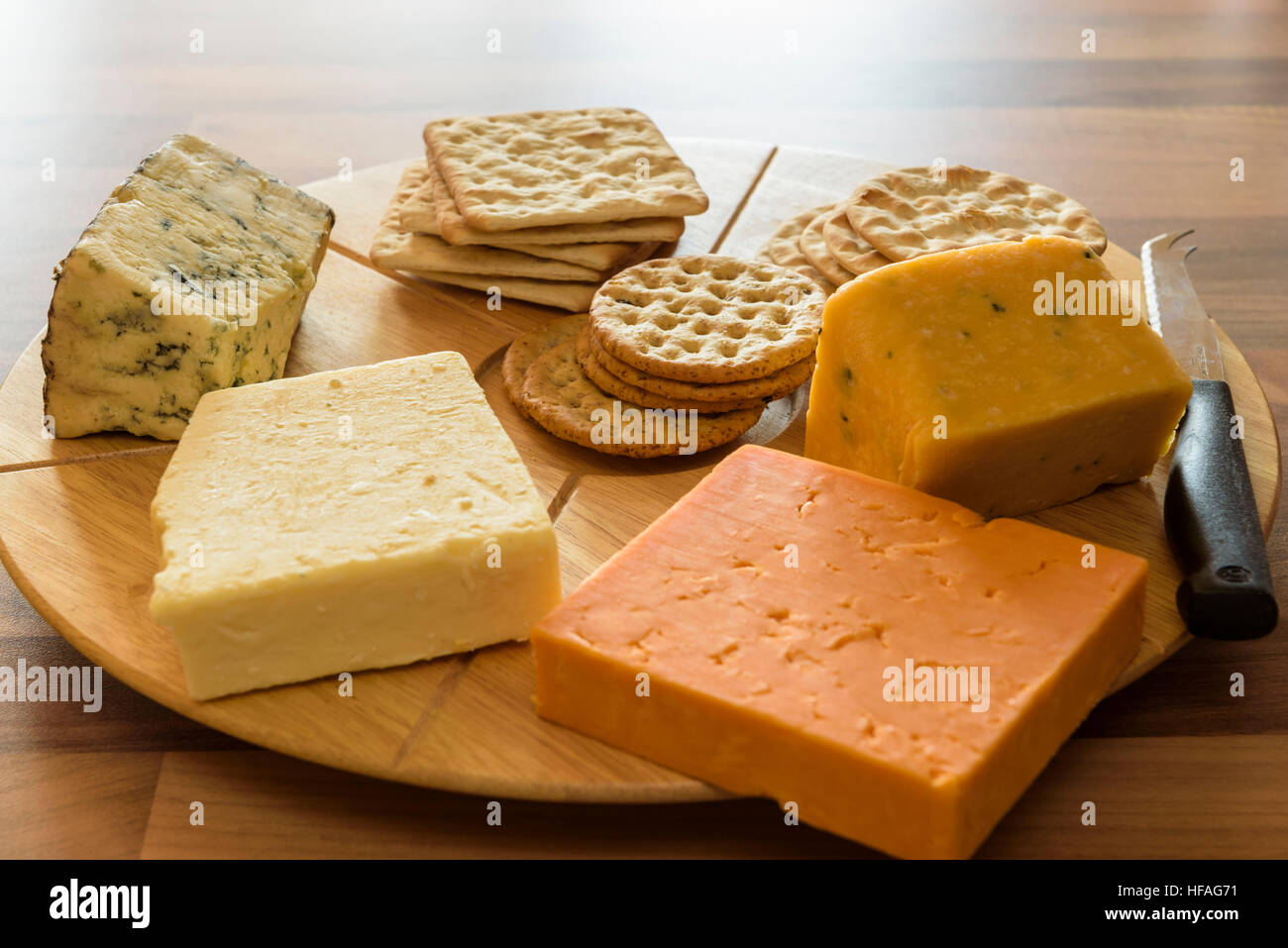 Assortment  of cheeses on a round wooden cheese board. - Stock Image