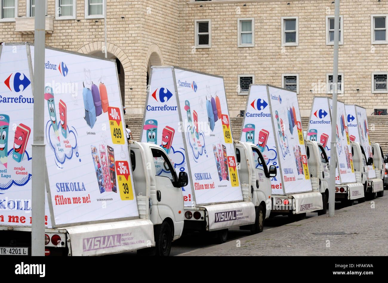 Five mobile advertising vans with posters for Carrefour in the centre of Tirana with the slogan 'Shkolla fillon - Stock Image