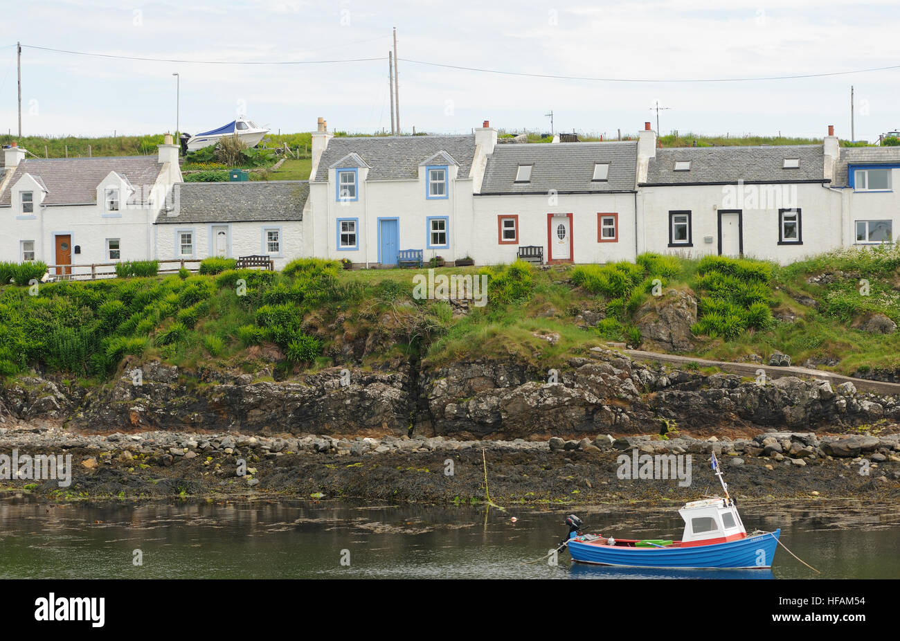A row of painted cottages on the edge of the sheltered harbour at Portnahaven. Portnahaven, Islay, Inner Hebrides, - Stock Image