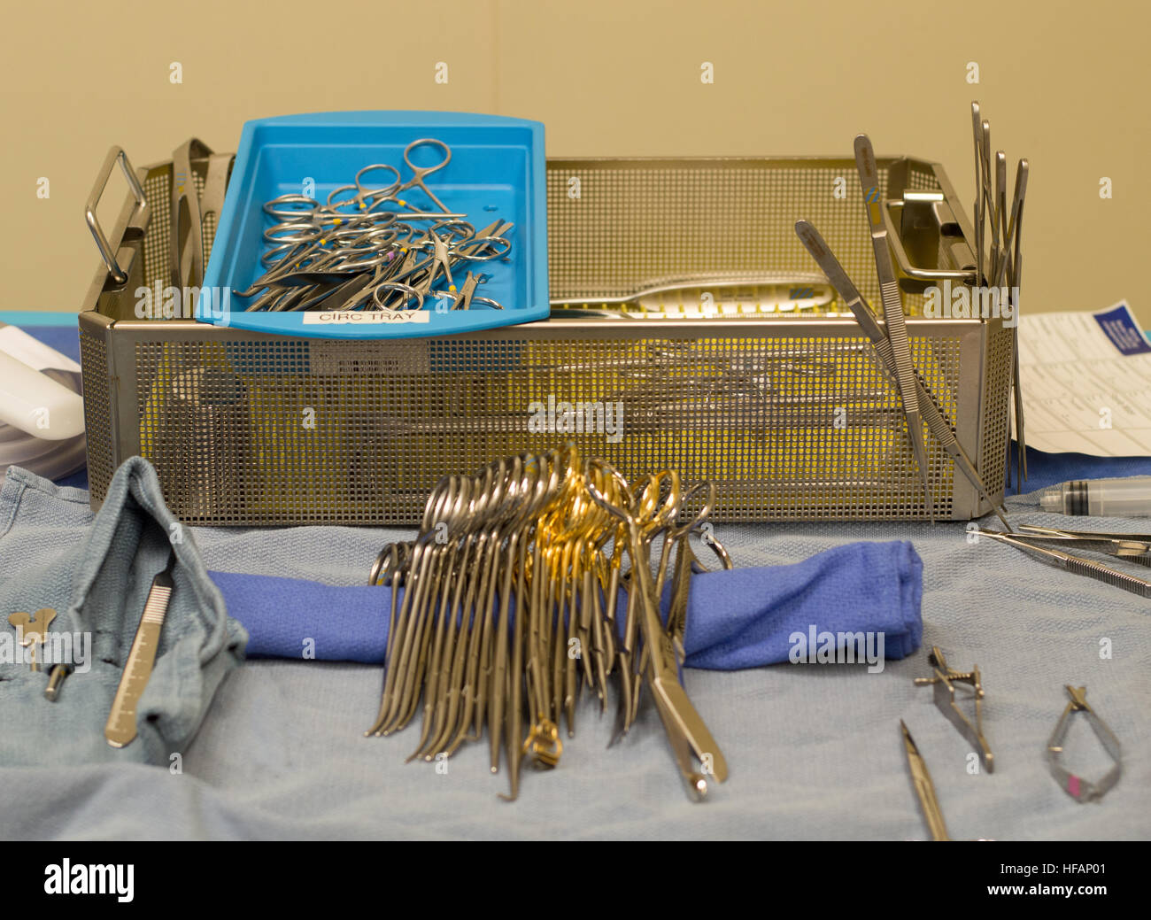 Sterile surgical instruments with a metal pan in background and sterile drapes on operating room table in foreground. - Stock Image