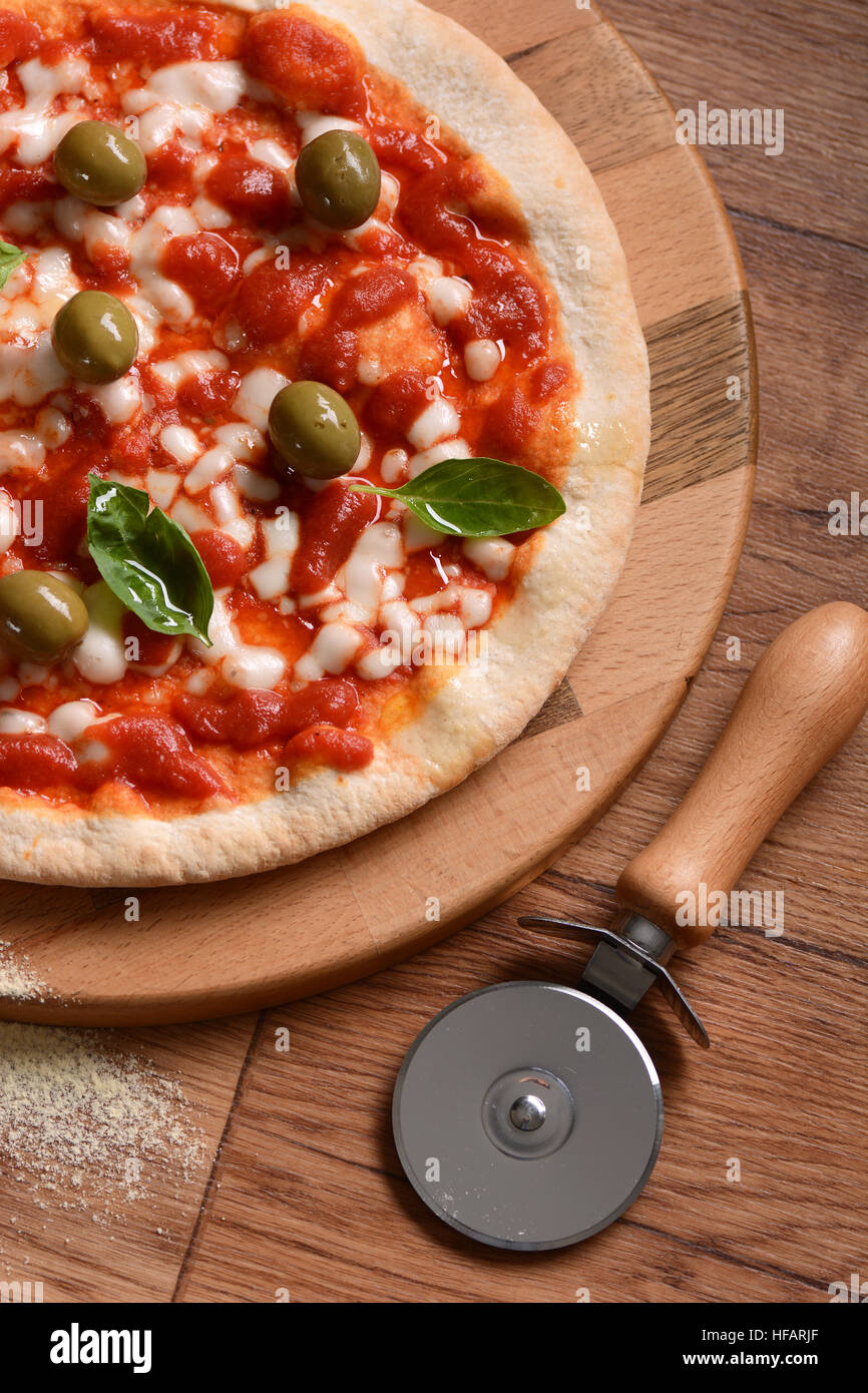 Italian pizza with green olives on cutting board Stock Photo