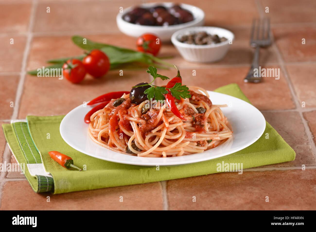 Spaghetti puttanesca - Traditional Italian recipe with anchovies, capers, tomato and chilli - Stock Image