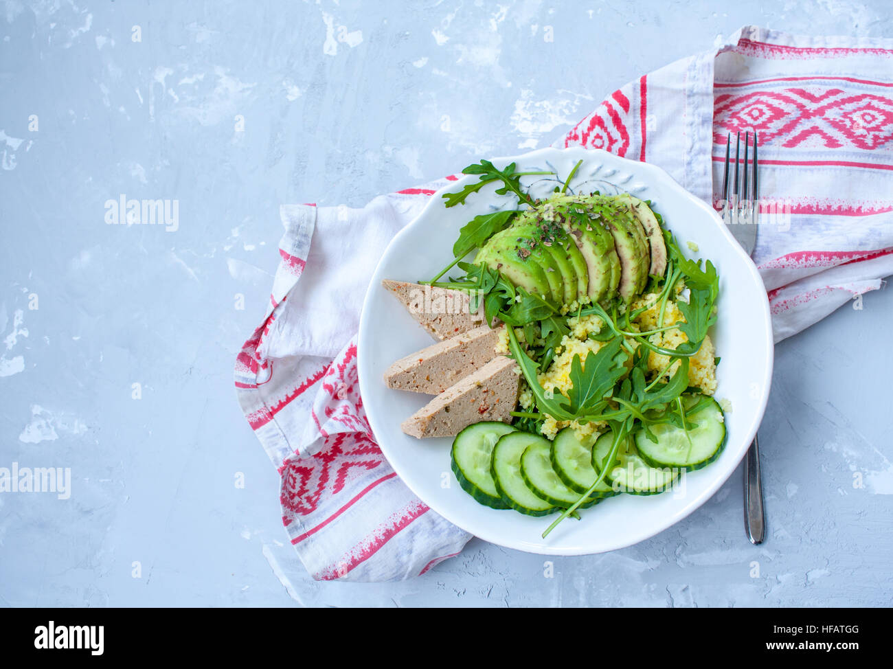 Green salad with avocado, couscous and tofu. Love for a healthy raw food concept. - Stock Image