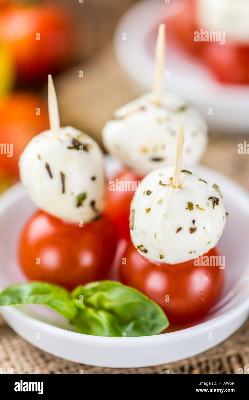 Tomatoes and Mozzarella with fresh Basil (selective focus) on an old wooden table - Stock Image