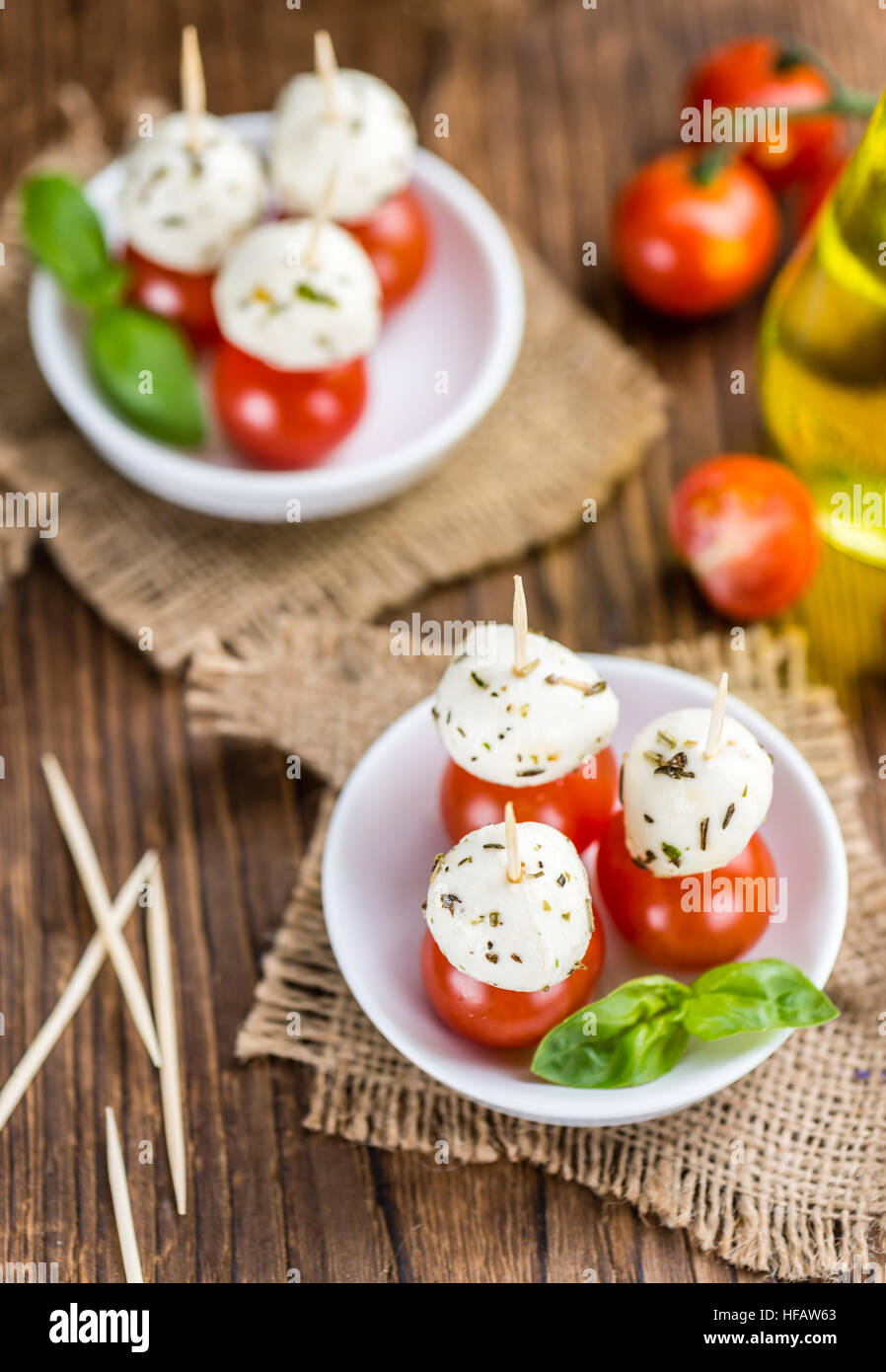Portion of Mozzarella with Tomatoes on an old wooden table (selective focus) - Stock Image