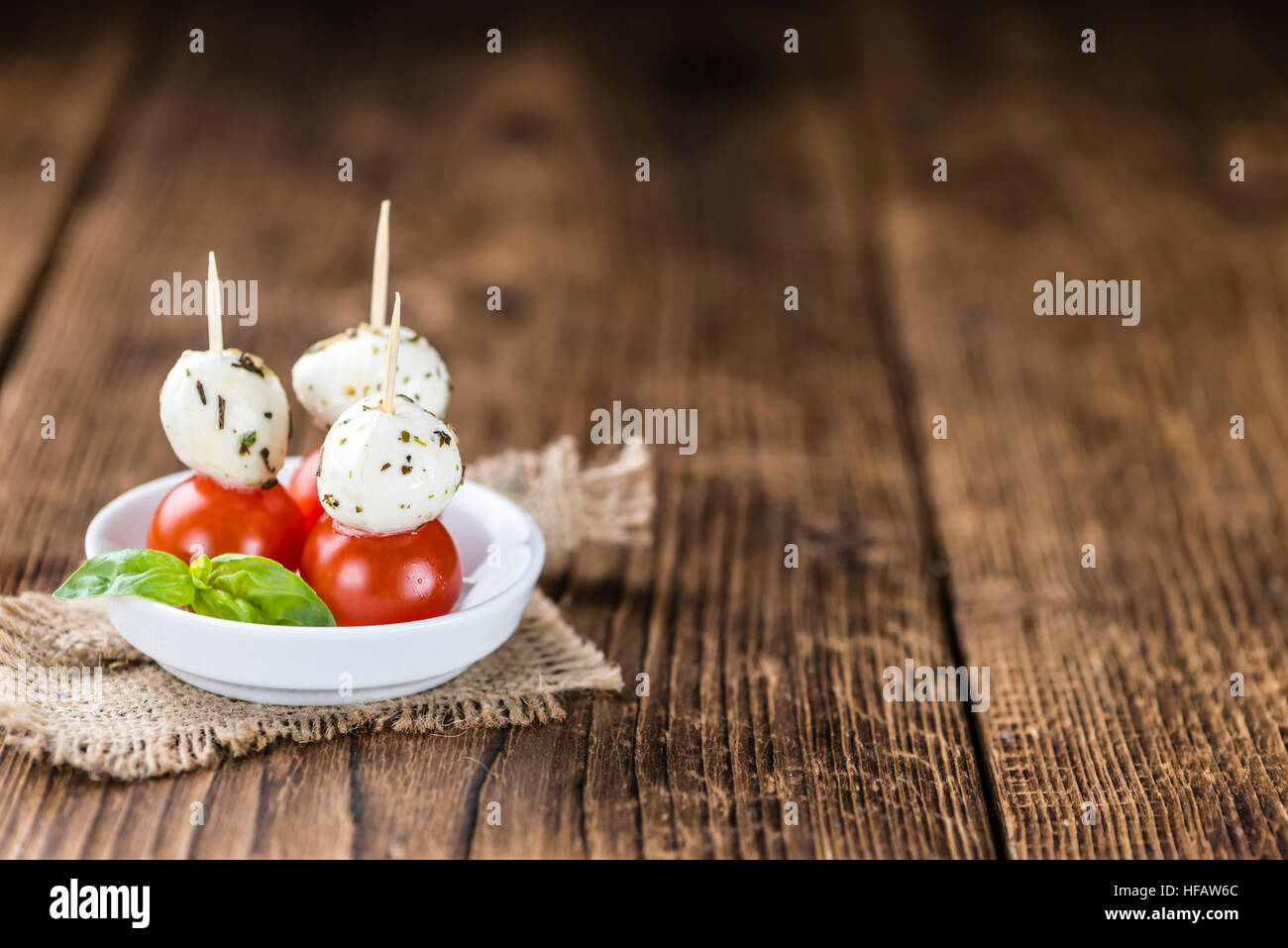 Mozzarella balls with Tomatoes (selective focus) on wooden background - Stock Image