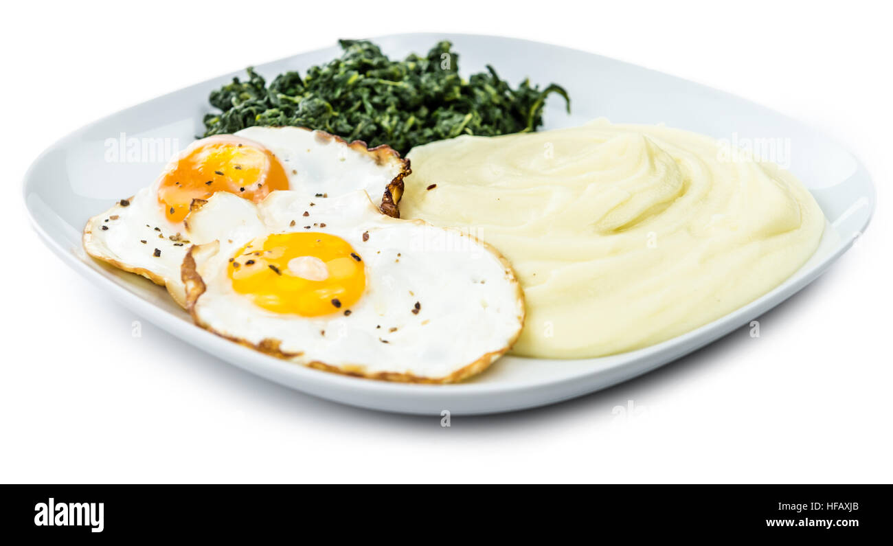 Fresh made Mash with fried eggs and spinach isolated on white background (close-up shot) - Stock Image