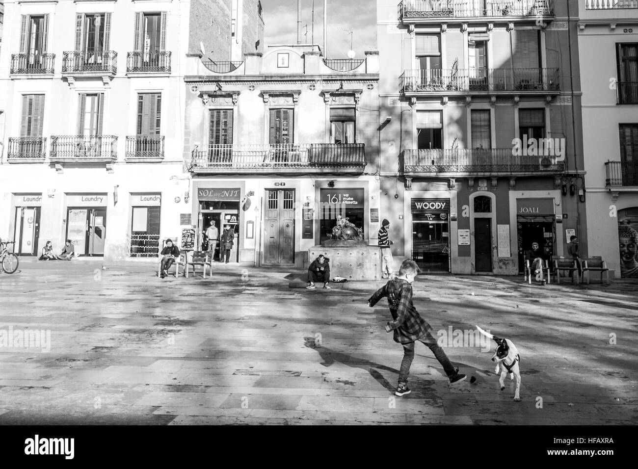 A boy plays with his dog in a european square in Barcelona Spain - Stock Image