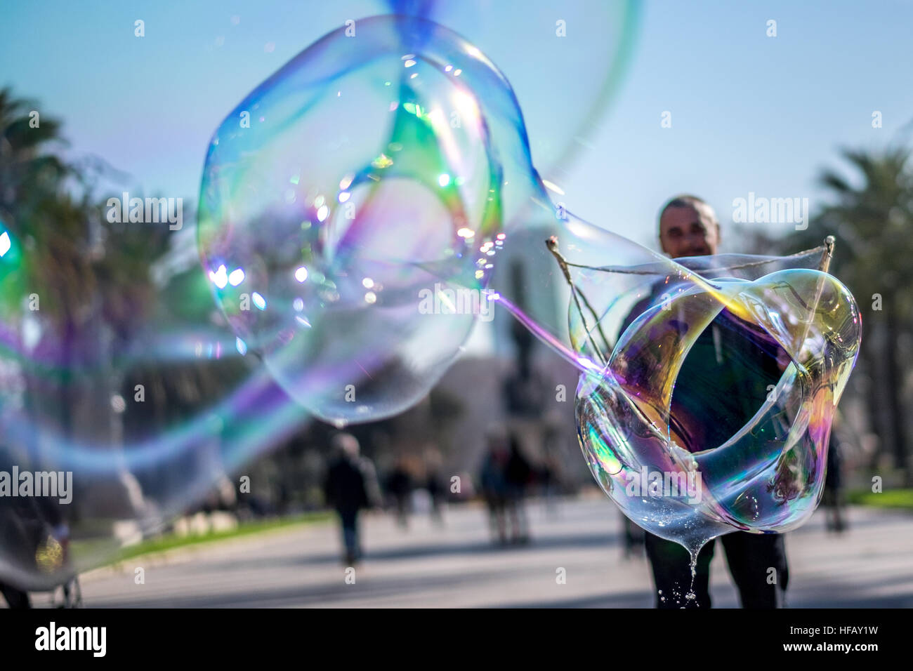 A man makes a huge soap bubble in a park. - Stock Image