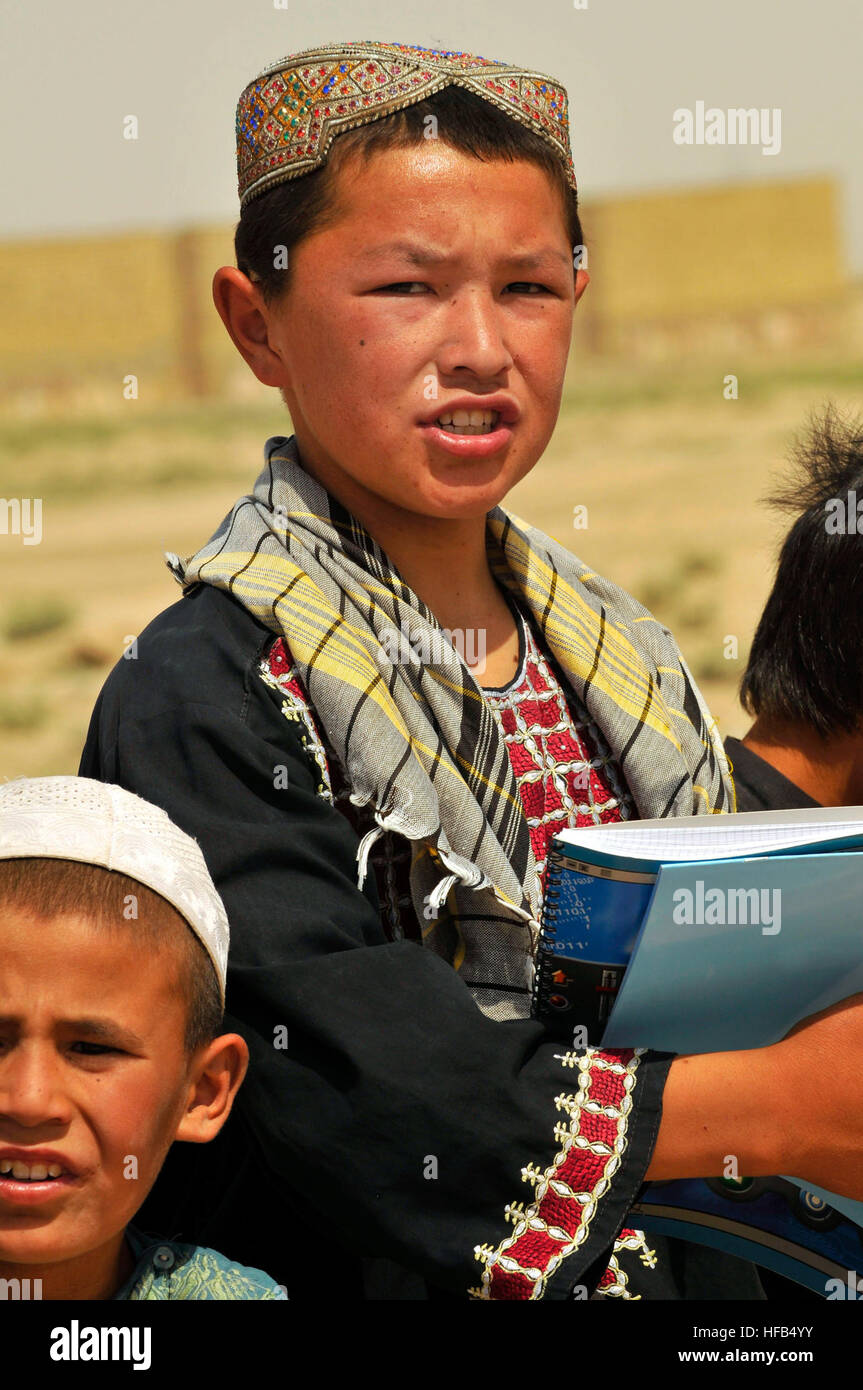 A young Afghan boy from the Homaro Faroq Village near Camp Marmal, Regional Command North, stands with his schoolmates - Stock Image