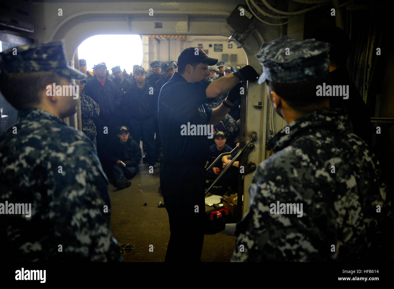 Damage Controlman 1st Class (SW/AW) Edward Carriero trains Sailors aboard the aircraft carrier USS Nimitz on maintenance - Stock Image