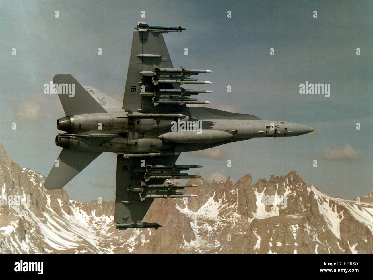 An underside view of an Air Test and Evaluation Squadron 4 (VX-4) F/A-18C Hornet aircraft in-flight.  VX-4 is testing - Stock Image