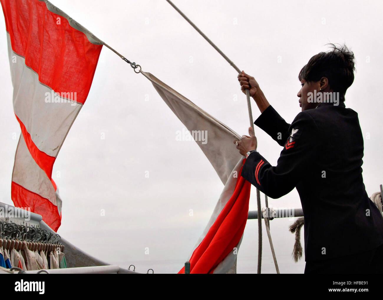 Petty Officer 2nd Class Angela Everett hoists a 'Code Hotel' flag aboard the amphibious dock landing ship - Stock Image